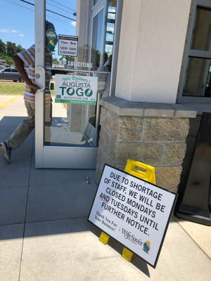 A customer enters the WifeSaver restaurant on North Leg in Augusta on Thursday, past a sign announcing that the location is closed Mondays and Tuesdays because of labor shortages.
