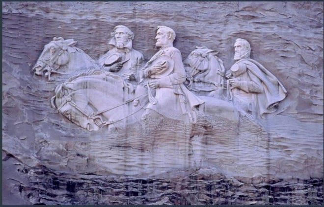 """Confederate President Jefferson Davis (from left) and Confederate Generals Robert E. Lee and Thomas """"Stonewall"""" Jackson are carved into the side of Stone Mountain."""