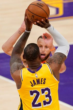 Los Angeles Lakers forward LeBron James hits a three-pointer shortly after being poked in the eye against Golden State on Wednesday.