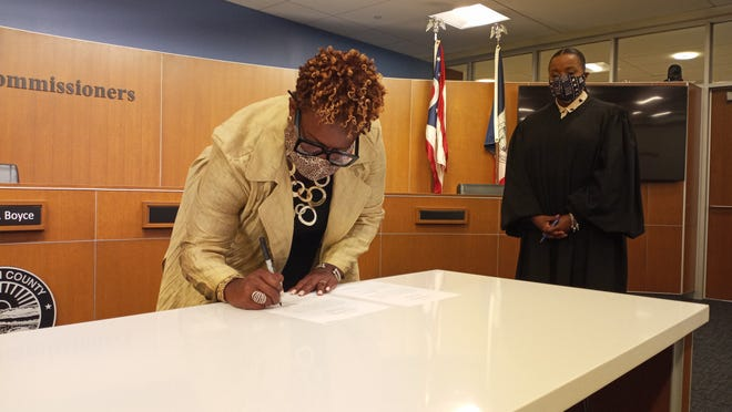 Dawn Tyler Lee signs the paperwork as Franklin County Common Pleas Judge Kimberly Cocroft watches Friday afternoon.