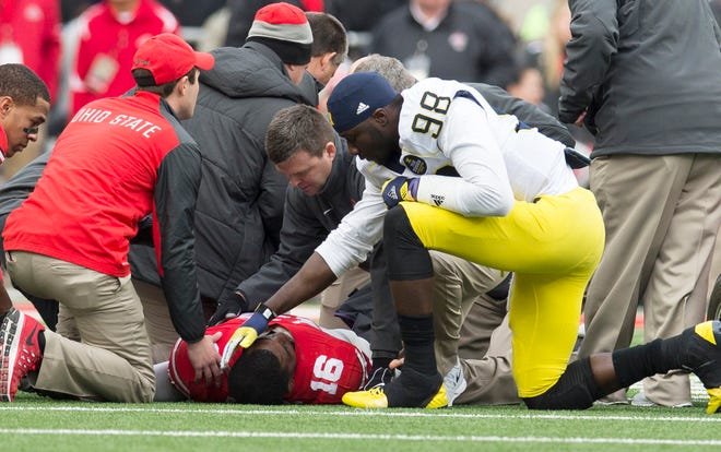 Dr. James Borchers, here tending to injured Ohio State quarterback J.T. Barrett  while Michigan quarterback Devin Gardner talks to Barrett during a game in 2014,  spearheaded a push to show that the 2020 season could be played with manageable risks.