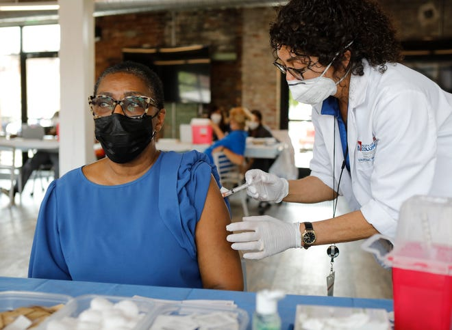 """JoAnn Rogers of the Brewery District gets a COVID-19 vaccination from nurse Rebecca Doss during the Columbus Public Health drop-in clinic at Stonewall Columbus in the Short North on Thursday, May 20, 2021. Several Short North Arts District restaurants offered discounts or free menu items for those who showed their vaccination card from the """"Vax and Relax"""" event."""