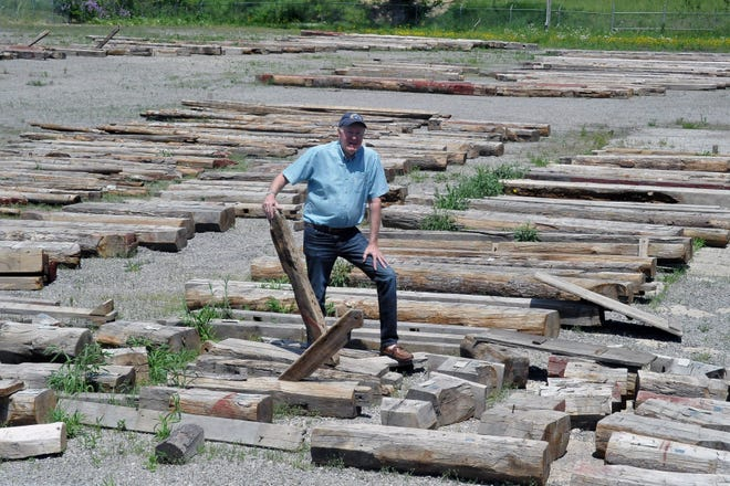 Paul Locher stands among the hundreds of logs from the former Buchholz barn that was deconstructed to make room for the new Wooster High School and will soon be reassembled at the Buckeye Agricultural Museum and Education Center.