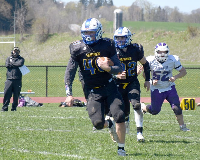 Isaiah Trago runs with the ball for Mt. Markham during a May 1 football game against Little Falls.