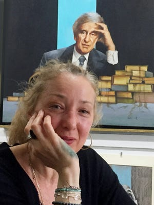 French artist Cécile Houel takes a break in front of her portrait of Nobel Prize Laureate Elie Wiesel, one of a series of Nobel winners Houel is creating for her ongoing collection. Houel will host an Open Studio event from 2 to 7 p.m. Saturday in her new studio on the third floor of the former YWCA building at 409 N. Fourth St. in Burlington. Other examples of Houel's work can be seen online at cecilehouel.com.