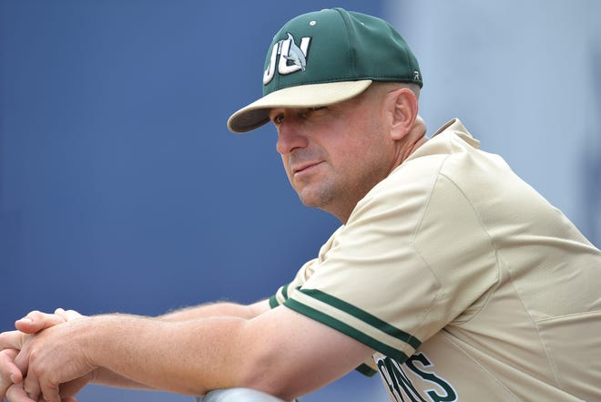 Jacksonville University head baseball coach Chris Hayes watches his team from the dugout.