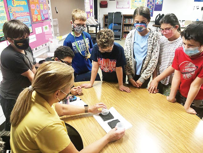An instructor from Kansas STARBASE demonstrates an experiment to fifth-graders at Linwood Elementary School.
