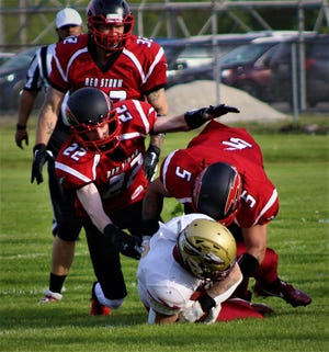 Southeast Michigan Red Storm cornerback  Logan Monaghan (22) and teammate Zac Drummonds (5) tackle a player for the Detroit Seminoles during the season opener on Saturday, May 15, 2021.