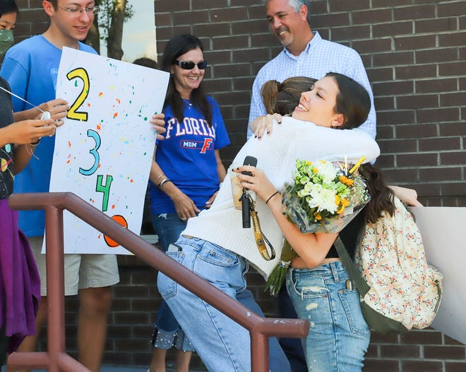 Niceville High  School Senior Laurel Wentworth is hugged by Emma Wagner on Friday as Laurel was greeted with a surprise celebration as she arrived for her final day of school. Lauren had a perfect attendance record in her 2,340-day school career.
