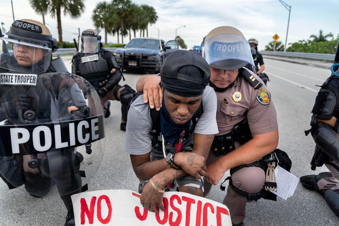 """""""Take a Knee"""" by The Palm Beach Post photographer Greg Lovett is included in the Palm Beach Photographic Centre's """"The New Normal: Covid Times"""" exhibition."""