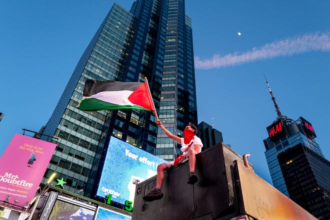 Supporters of the Palestinians march in New York's Time Square Thursday, May 20, 2021. Israel and Hamas announced a cease-fire, ending a bruising 11-day war that caused widespread destruction in the Gaza Strip and brought life in much of Israel to a standstill.
