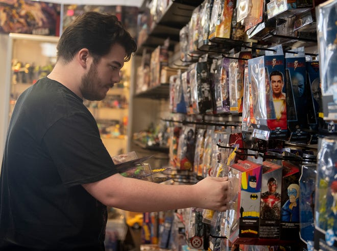 Cody Gum of Your Toy Connection in downtown Ravenna rearranges items at the store, which will allow guests to go maskless as of June 2. However, those who wish to continue wearing masks are also welcome to do so he said.