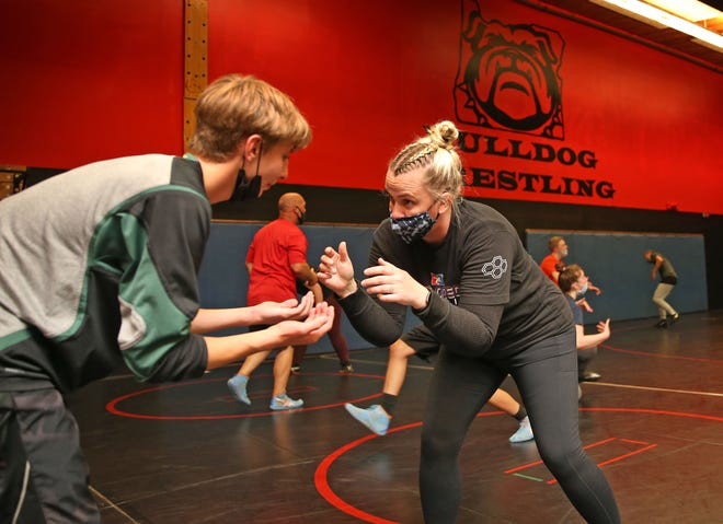 Christina Kent, right, the new wresting coach at Creswell High School, works on skills with Mason Barrett during practice.