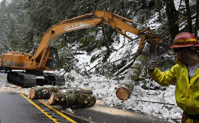 Workers use heavy machinery to clear logs from Highway 58 near mile marker 27 on Feb. 27, 2019. Hundreds of trees were downed along the roadway when 12 inches of heavy snowfall on Feb. 25, the start of four days of snow resulting in a whopping total of 18.8 inches and left hundreds without power for more than five days.