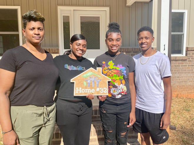 Chancey Clark, left, with her children Amiya Gullate, Ashley Gullate and Aspen Brown, celebrate the opening of Clark's new home in Vermont Village.
