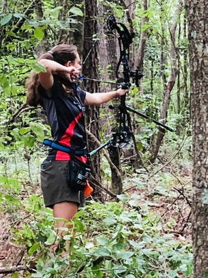 Olivia Poston shoots an arrow in the woods. Poston graduates from Pinnacle Classical Academy this week.