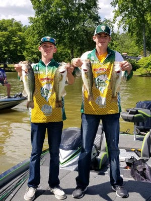 Members of the bass fishing team at Crest High School hold up their catches.
