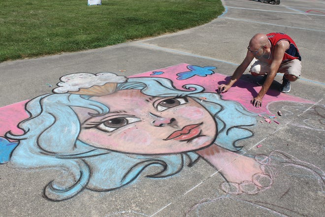A chalk artist from Iowa puts the finishing touches on a work at the 2019 Prairie Chicken Festival.