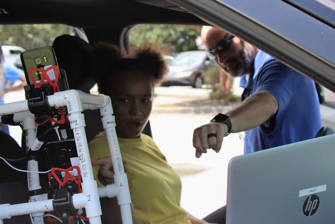 In a 2018 photo Ibn Simms, 14, a member of Brigade Boys & Girls Club, explores U.S. Cellular's engineering car as Jon Smith, optimization engineer for U.S. Cellular, demonstrates how the company's network operates and how he monitors it.