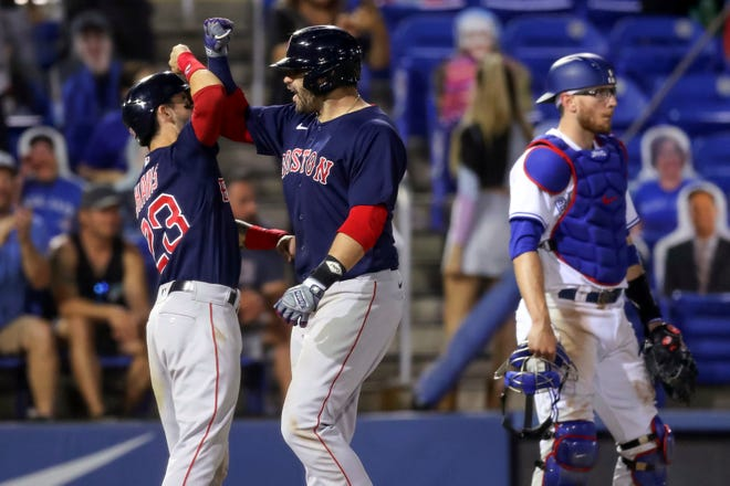 Boston Red Sox's J.D. Martinez, center, celebrates his two-run home run with Michael Chavis as Toronto Blue Jays catcher Danny Jansen stands near the plate during the Red Sox's 8-7 win in Dunedin, Fla.