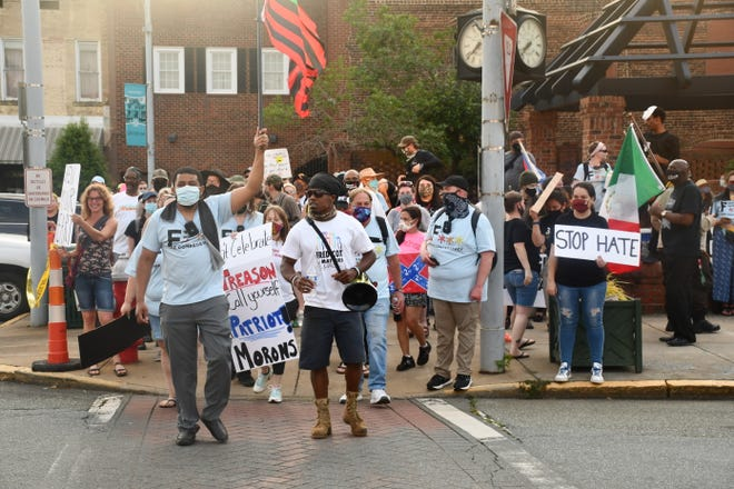 Counter-demonstrators take a lap around Court Square in Graham on Thursday, at the tail end of the Confederate memorial.
