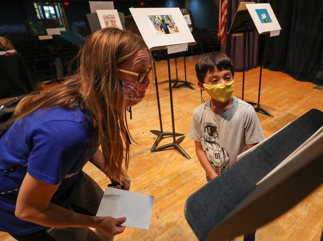 Grandview first-grader Harry Fox, 7, and his mother, Julie, discuss  the symbolism in artwork created Columbus artist Lisa McLymont and displayed at an exhibit called Amplify on May 16 at Grandview Heights High School. The exhibit was organized by junior Maria Sipes and sophomore Janira Skrbkova was to showcase artwork by local Black, Indigenous and people of color.