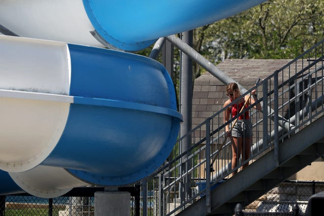 Lead lifeguard Emily Marschhausen scrubs the steps leading up to the slide at the Hilliard Family Aquatic Center on May 19 in preparation for the pool facility's reopening May 29.