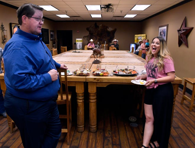"""Singer Ariel Hutchins reacts Thursday after learning her single """"Wine Won't Work"""" is the first by a female single to debut at No.1 on the Texas Regional Radio Report. Disc Jockey J.B. Cloud, (left) provided the good news."""