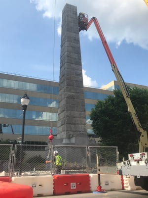 Contractors continue to work to dismantle the Vance Monument on Friday.