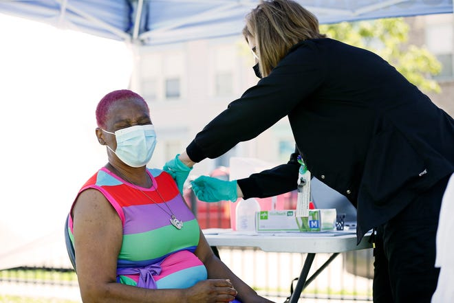 Mildred Godfrey, of West End, winces as she receives her first dose of the Pfizer COVID vaccine from nurse Donna Cunha during a walk-up vaccination event hosted by Cincinnati Children's Hospital at Laurel Playground in the West End neighborhood of Cincinnati on Friday, May 21, 2021.