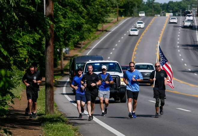 Officers escorted by a police truck and van to support them jog up the right lane during the Clarksville Police Department's stretch of the Law Enforcement Torch Run with the Flame of Hope to support Tennessee Special Olympics along Madison Street in Clarksville, Tenn., on Friday, May 21, 2021.