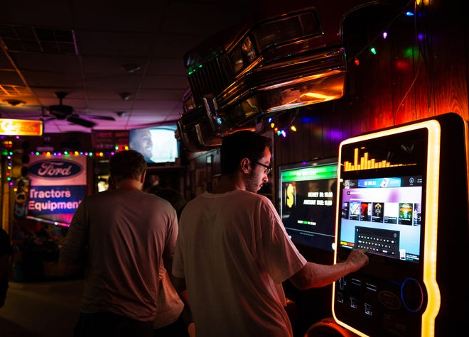 Cutsomers use an internet jukebox at Gusoline Alley in Detroit on July 20, 2018. Gusoline Alley's old jukebox was legendary, but the bar switched to an internet jukebox to keep up with the times.