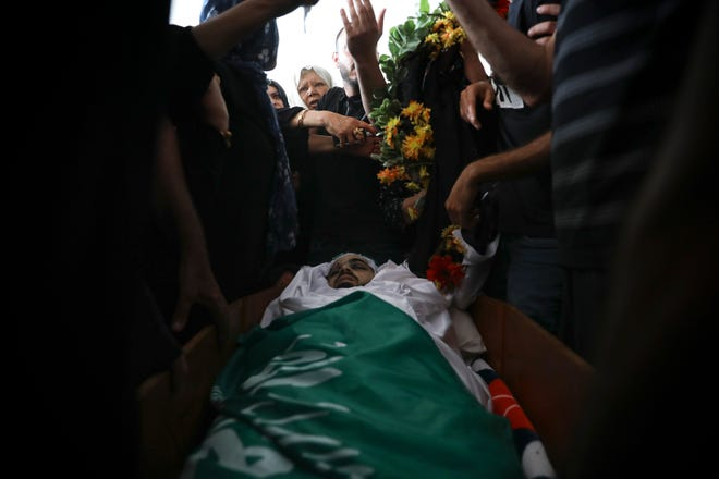Palestinian mourners gather around the body of Mohammad Kiwan, 17, whose family says he was killed in clashes with Israeli police in the Arab town of Umm al-Fahm, Thursday, May 20, 2021.
