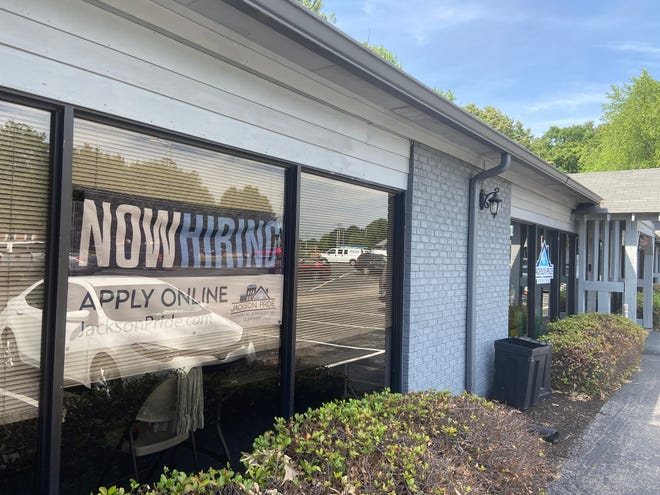 """Jackson Pride cleaning has a """"NOW HIRING"""" sign on the front window of its office building on North Parkway."""