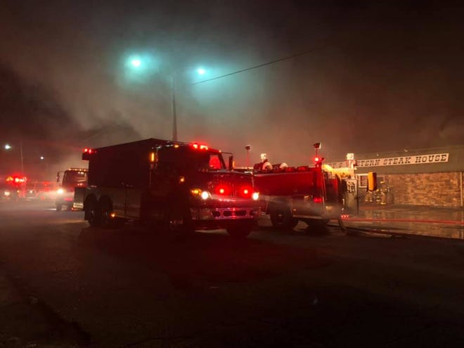 Fire trucks sit in the front parking lot of the Country and Western Steak House in Camden as fire fighters work to put out a fire early Friday morning.