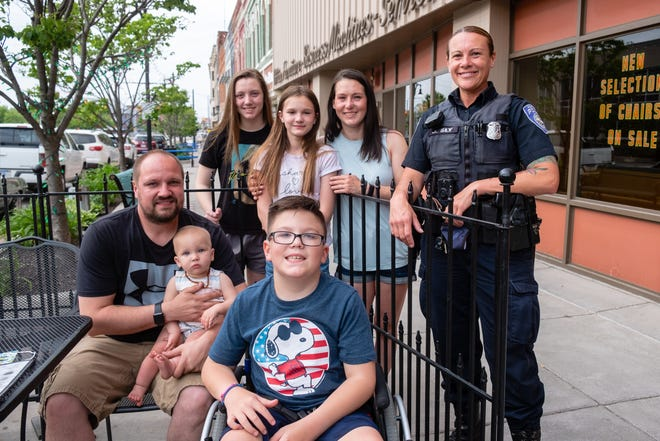 Mason Warner, center, and his family pose for a portrait with Port Huron Police Officer Jennifer Sly Thursday, May 20, 2021, outside The Raven Cafe in Port Huron. Mason has cerebral palsy, hydrocephalus and chronic lung disease. Sly is helping the family raise money for a new wheelchair-accessible vehicle.