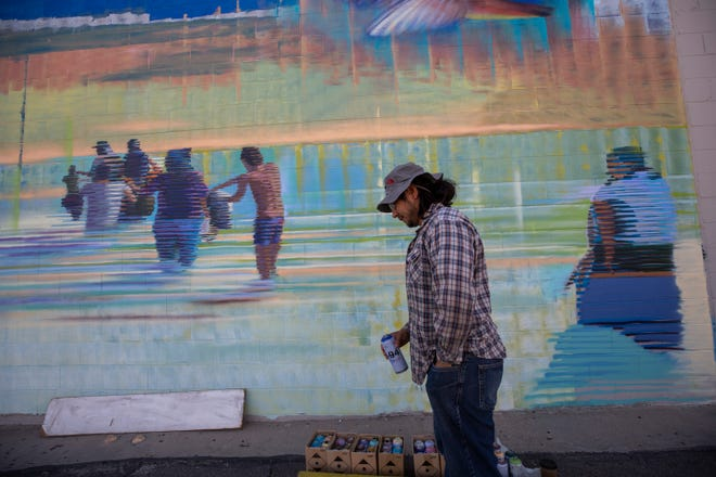 """El Paso artist Victor """"Mask"""" Casas paints a mural that  depicts migratory species familiar along the border region, including humans. The mural is on the western wall of Carlos' Bakery in Sunland Park, New Mexico."""