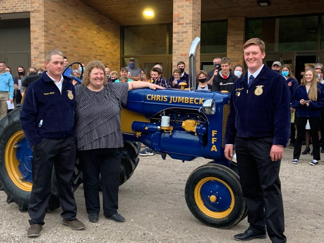 Retiring Ag teacher Chris Jumbeck, center, from Cochrane-Fountain City was presented with a restored blue and gold painted antique tractor in honor of her retirement after 33 years influencing youth at the school. Joining her are Trevor Adank and Philip Krzyszton, right.