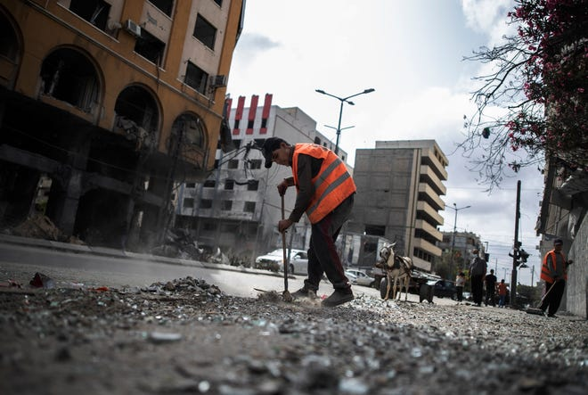 Palestinian municipal workers clean the streets following a cease-fire reached after an 11-day war between Gaza's Hamas rulers and Israel, in Gaza City, Friday, May 21, 2021.