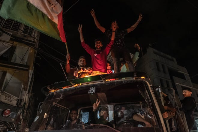 Palestinians celebrate the cease-fire agreement between Israel and Hamas on May 21 in Gaza City.
