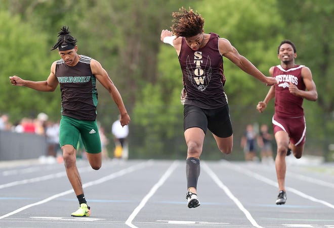 Xavier Preston of Stow, center, runs to a first-place finish in the 200-meter dash between Jonathan Banks, left, of Nordonia and Nushawn Grant of Maple Heights during the Division I district track meet at Nordonia High School on Friday. [Karen Schiely/Beacon Journal]