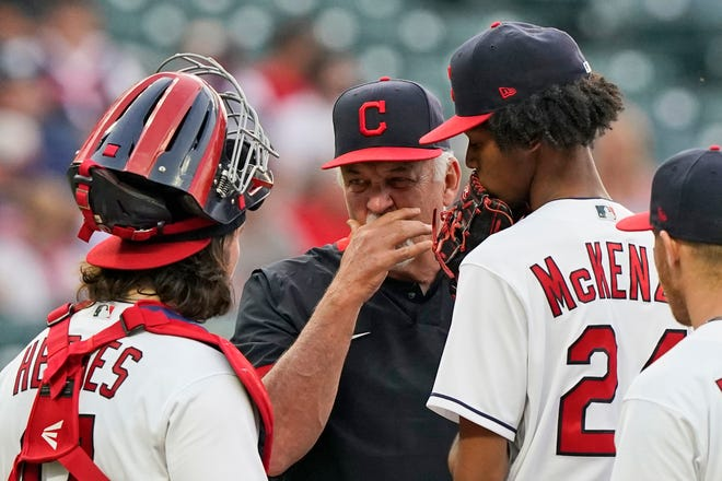 Cleveland pitching coach Carl Willis, center, taels with starting pitcher Triston McKenzie, right, and catcher Austin Hedges in the fourth inning of a baseball game, Friday, May 21, 2021, in Cleveland. (AP Photo/Tony Dejak)