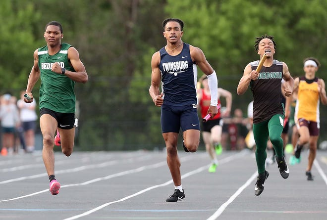 Drevon Trapp, left, of Bedford anchors his team to a first place finish in the 4x400 meter relay past Alexander Branch of Twinsburg and Daylon Brown of Nordonia during the Div. I District Track Meet at Nordonia High School Friday, May 21, 2021 in Macedonia, Ohio.