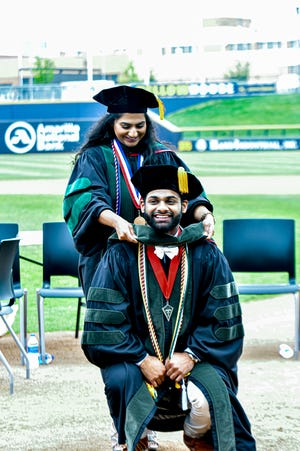 Steven Philip is hooded by his sister Stacy at the commencement ceremony for the Texas Tech University Health Sciences Center Jerry H. Hodge School of Pharmacy Saturday at Hodgetown.
