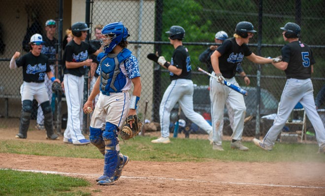 Ellwood City catcher James Meehan holds the ball as South Park players celebrate their seven-run fifth inning. [Lucy Schaly/For BCT]