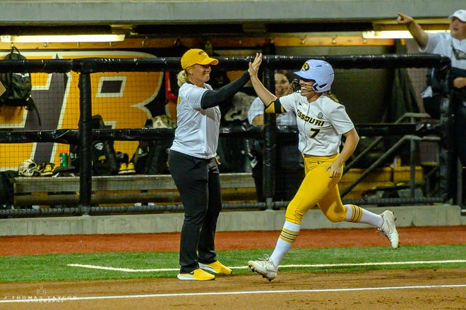 Missouri head coach Larissa Anderson high-fives senior Brooke Wilmes (7) as she rounds third base after hitting a home run in the first inning Friday during an NCAA regional game at Mizzou Softball Stadium.