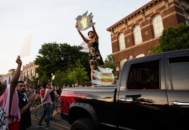 """""""Storm"""", an organizer with the """"Damn Girl"""" Roll Out Protest Ride, hands out protest signs that support the pro-Palestine movement as part of a crowd that traveled north on High Street from Goodale Park to support the liberation of Palestine in Columbus, Ohio on May 22, 2021."""