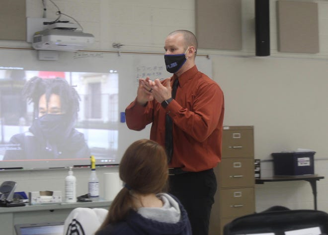 Adrian High School social studies teacher Jason Skeels is pictured wearing a mask while teaching Jan. 20. Teachers, students and staff are being required to continue to wear masks at school, though the U.S. Centers for Disease Control and Prevention has said fully vaccinated people do not need to wear masks.