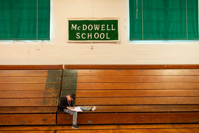 Tony Magallon, 8, draws inside the McDowell Elementary School gymnasium as he waits for his bus to pick him up from the Columbia, Tenn., School on Thursday, May 20, 2021. The school closed for good on May 24.