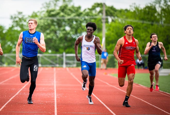 Truman's Patrick Martin, second from right, and Grain Valley's Cole Keller, left, dash to the finish line while competing in the 400 meters in the Class 5 Sectional 4 meet Friday, Martin won and Keller was second as both advanced to the state meet.